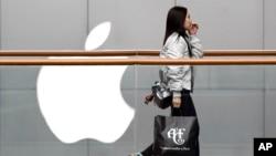 在北京一個購物中心,一名女子提著美國服裝品牌Abercrombie & Fitch的購物袋走過蘋果商店(2019年2月26日)