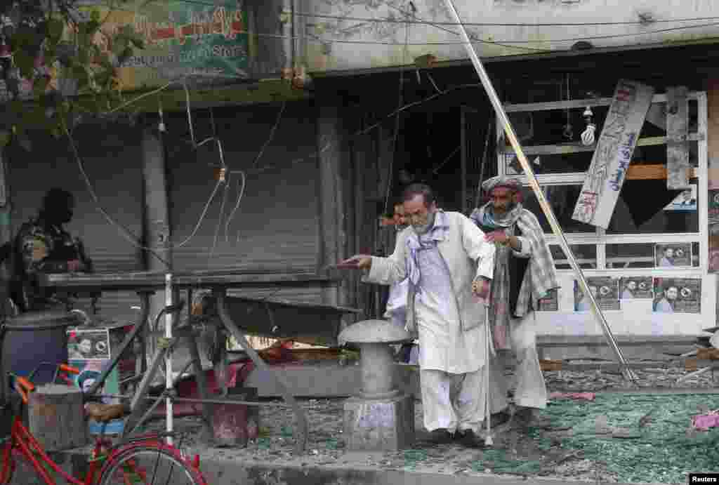 Afghan residents leave the site of a suicide car bomb attack in Jalalabad province, Afghanistan, March 20, 2014.