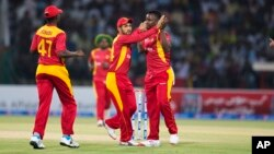 Zimbabwe players celebrate the dismissal of Pakistan's Ahmed Shahzad during a match at the Gaddafi Stadium in Lahore, Pakistan, Sunday, May 24, 2015. (AP Photo/B.K. Bangash)