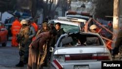 Fawad, pegawai restoran Lebanon yang terluka dalam ledakan bom bunuh diri di luar restoran, mengamati kendaraan yang rusak dekat restoran tersebut di Kabul 18 Januari 2014. 15 orang tewas, sebagian besar orang asing.