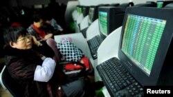 11일 중국 산둥성 칭다오 시 증권거래소에서 투자가들이 컴퓨터 스크린으로 증시 현황을 지켜보고 있다.