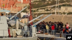 Migrants arrive at the Lampedusa island harbor Sunday, May 3, 2015.