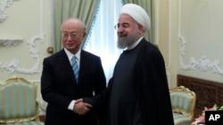Presiden Iran Hassan Rouhani (kanan) menerima kunjungan Dirjen IAEA, Yukiya Amano dalam pertemuan di Teheran, Iran hari Minggu (18/12).