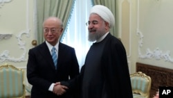 In this photo released by official website of the office of the Iranian Presidency, President Hassan Rouhani, right, and Director General of the International Atomic Energy Agency, IAEA, Yukiya Amano shake hands for media at the start of their meeting at