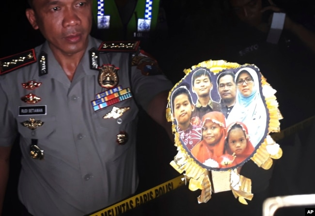 FILE - Surabaya Police Chief Col. Rudi Setiawan shows a picture of the family of Dita Oepriarto who carried out the church attacks on May 13, 2018 in Surabaya, East Java, Indonesia.