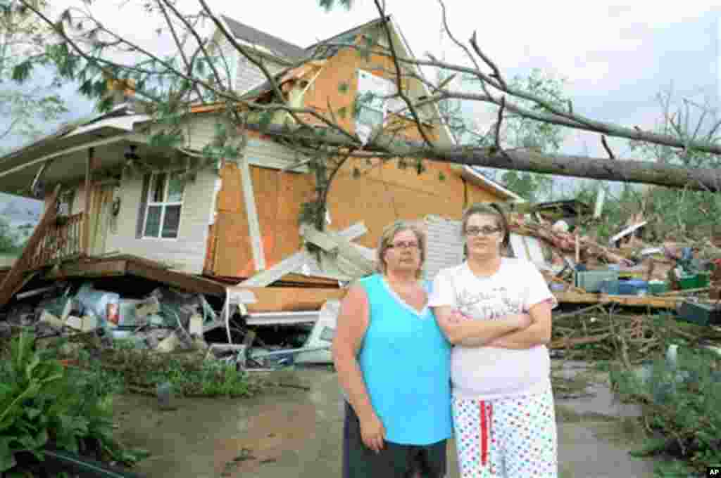 Diane and Ashley Guyton, victims of the tornado that ripped through Concord, Ala., pose for a photo in front of their house, Thursday, April 28, 2011. The gray truck, underneath the home, saved their lives. Diane and Ashley ran with their family to the ba