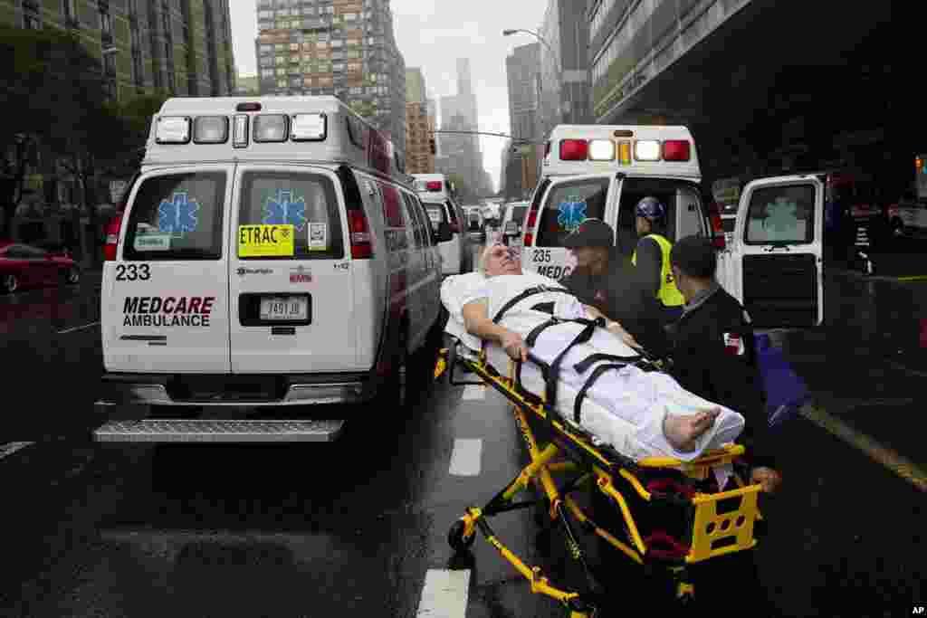 Un paciente es trasladado en una ambulancia en plena lluvia durante la evacuación del centro médico New York University Tisch Medical en Nueva York. }