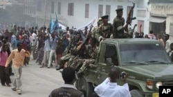Somali government soldiers pass angry demonstrators gather at southern Mogadishu's presidential palace to protest against the anticipated resignation of the Somali prime minister in Mogadishu, Somalia, June 9, 2011