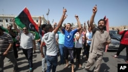 Libyans hold up their ink-marked fingers that shows they have voted as they celebrate in Martyrs' Square in Tripoli, Libya, Saturday, July 7, 2012.