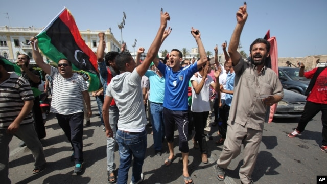 Libyans hold up their ink-marked fingers that shows they have voted as they celebrate in Martyrs' Square in Tripoli, July 7, 2012.