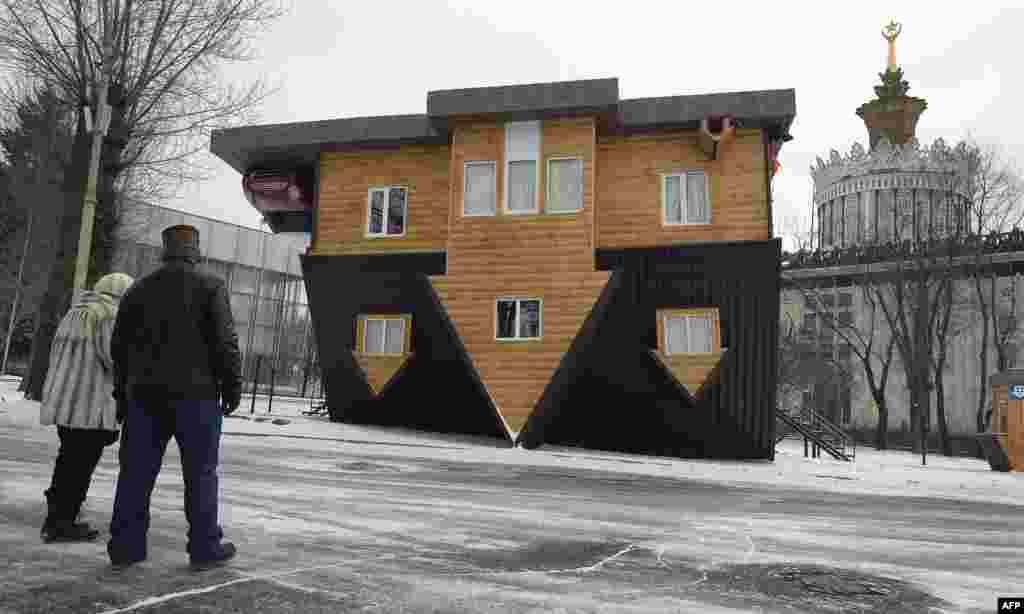 """Pengunjung melihat sebuah """"rumah terbalik"""" dalam pameran di Moskow, Rusia."""