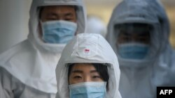 In this photo taken on March 12, 2020, medical workers wearing protective clothing against the COVID-19 novel coronavirus walk to a decontamination area at the Keimyung University hospital in Daegu. - South Korea -- once the largest coronavirus outbreak o