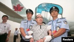 FILE - Chinese fugitive Lai Changxing is escorted back to Beijing from Canada, at Beijing International Airport, July 23, 2011.