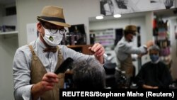France, Mayenne, French hairdresser Marc Mauny tends to his first customer during the re-opening