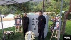 2019年10月18日,赵紫阳夫妇墓碑前摆放着出席骨灰安葬仪式的亲友们献的鲜花。赵紫阳之子赵二军(右)立于碑前。(美国之音艾伦拍摄)