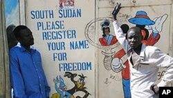 Des jeunes soudanais à côté d'une affiche exhortant les Sud-Soudanais à s'incrire pour voter lors du référendum