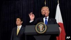 Presiden AS, Donald Trump, berbicara dengan PM Jepang, Shinzo Abe, yang menyimak saat mereka berdua mengeluarkan pernyataan terkait Korea Utara di Mar-a-Lago (11/2). Palm Beach, Florida, AS. (foto: AP Photo/Susan Walsh).