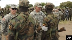 In this April 20, 2011 file photo, U.S. Army soldiers are seen with Uganda People's Defence Force soldiers at the closing ceremony for operation ATLAS DROP 11, an annual joint aerial delivery exercise, in Soroti, Uganda. While putting few U.S.