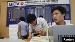 Nhân viên đếm tiền tại một chi nhánh của Ngân hàng BIDV tại Hà Nội