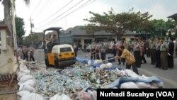 Satuan Pamong Praja Kabupaten Sleman memusnahkan berbagai macam minuman keras hasil operasi beberapa waktu lalu, namun tidak bisa menghentikan konsumsi oplosan. (VOA/Nurhadi)