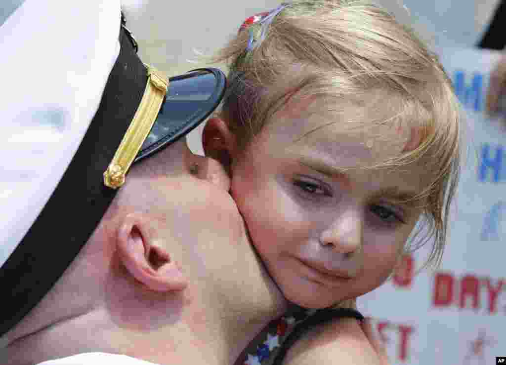 Five-year-old Adley Lausch, cries as she gets a kiss from her father, Lt., Adam Lausch, after he disembarked the nuclear powered aircraft carrier USS Harry S. Truman at Naval Station Norfolk in Norfolk, Virginia, July 13, 2016.