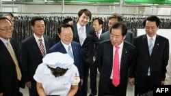 Chủ tịch đảng Quốc Ðại Hong Joon-pyo (thứ nhì từ phải) nhìn một công nhân Bắc Triều Tiên đang làm việc khi ông đến thăm một xí nghiệp trong khu công nghiệp Kaeson hôm 30/9/11