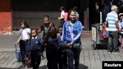 Yon dam kap mache ak yon gwoup timoun apre lekòl fin lage nan Karakas, Venezuela. 3 avril 2019. Foto: REUTERS/Manaure Quintero NO