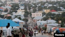 FILE - People walk along a street in Mogadishu, Somalia, Sept. 28, 2013.