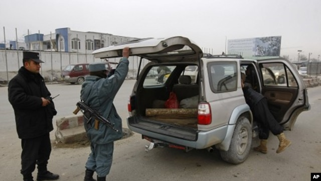 Afghan policemen search a car at a check point in Kabul, February 26, 2012.