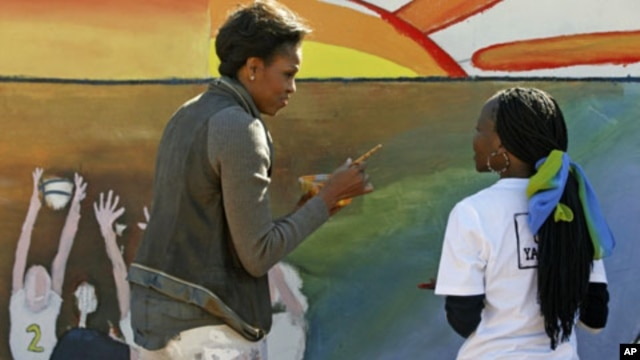 U.S. first lady Michelle Obama, left, paints a mural with youths at Botswana-Baylor Adolescent Center which offers teenagers with HIV support, Gaborone, Botswana, Friday, June 24, 2011