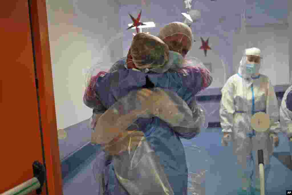 Ela Gubbiotti hugs her partner Giancarlo Vannimartini, an anesthesiologist who has been hospitalized for 10 days, in a safe room where patients and relatives can hug each other protected by a plastic film screen set up inside the COVID-19 ward of the Ospedale dei Castelli Hospital in Ariccia, near Rome, Italy.