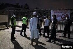 Beberapa polisi dengan mengenakan masker berjaga di luar masjid Seri Petaling di Kuala Lumpur yang menjadi salah satu sumber perebakan virus corona di Malaysia dan kini ditutup sementara (17/3).