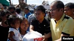 ဖိလစ္ပိုင္သမၼတ Benigno Aquino (ယာ) မုန္တိုင္းကယ္ဆယ္ေရးပစၥည္းေတြ ဒုကၡသည္ေတြကို ေဝငွေပးစဥ္။ (ႏုိဝင္ဘာ ၁၈၊ ၂၀၁၃)