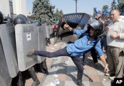 Ukrainian protesters clash with police after a vote to give greater powers to the east, outside the Parliament, Kyiv, Ukraine, Aug. 31, 2015.