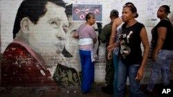 Personas buscan sus nombres en el padrón electoral cerca de un mural dedicado a Hugo Chávez, el domingo, durante las elecciones municipales en Caracas.