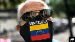 Un hombre usa una mascarilla con la bandera de Venezuela, mientras espera para llenar el tanque de su automóvil en una estación en Caracas, Venezuela. Mayo 25, 2021. Foto: AP.