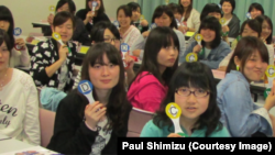 Students at a university in Japan use interactive response paddles during an activity.