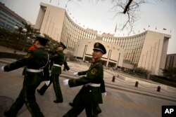 FILE - Chinese paramilitary police march past China's central bank, the People's Bank of China, in Beijing, March 12, 2016.