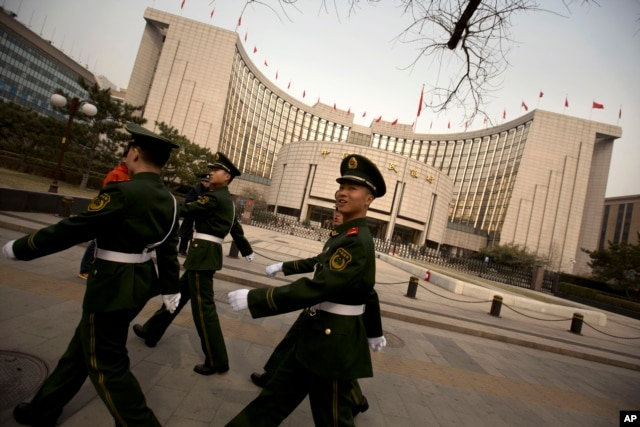 Chinese paramilitary police march past China's central bank, the People's Bank of China, in Beijing, Saturday, March 12, 2016. In a new effort to dispel anxiety about China's cooling economy, the central bank governor said Saturday the country can hit this year's official growth target and Beijing has no need to weaken its currency to boost sagging exports.