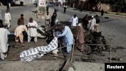 巴基斯坦奎达的警察和救援人员掩盖在爆炸中丧生者的尸体,2017年6月23日