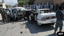 Afghan security forces inspect the wreckage at the site of a roadside bomb explosion in Jalalabad August 4, 2013.