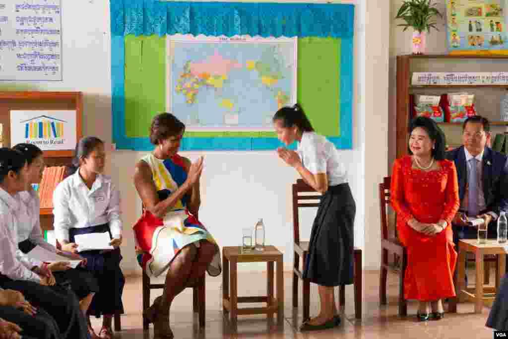 """លោកស្រី Michelle Obama ភរិយាលោកប្រធានាធិបតីសហរដ្ឋអាមេរិកពិភាក្សាជាមួយសិស្សស្រីខ្មែរនៅវិទ្យាល័យហ៊ុន សែនប្រាសាទបាគងនៅជាងក្រុងសៀមរាប កាលពីព្រឹកថ្ងៃសៅរ៍ទី២១ ខែមីនា ឆ្នាំ២០១៥ ដោយមានវត្តមានលោកស្រីប៊ុន រ៉ានី។ លោកស្រី Obama មានគោលដៅលើកស្ទួយកម្មវិធីអប់រំ «គម្រោងផ្តល់ឱកាសឲ្យសិស្សស្រីបានសិក្សា» ឬ """"Let Girls Learn""""។ (នៅ វណ្ណារិន/VOA)"""
