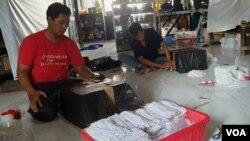 """Relawan """"Jatim for Indonesia"""" mengemas sejumlah bantuan untuk warga terdmpak corona di berbagai daerah (VOA/Petrus Riski)."""