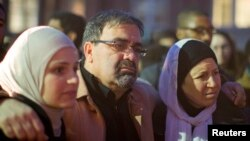 Namee Barakat with his wife, Layla (R) and daughter Suzanne, family of shooting victim Deah Shaddy Barakat, attend a vigil on the campus of the University of North Carolina in Chapel Hill, N.C., Feb. 11, 2015.