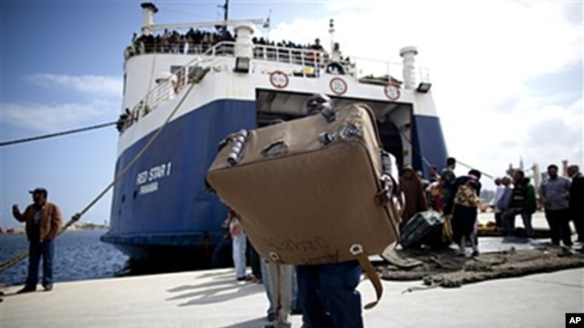 A migrant carries a suitcase after arriving at the port in Benghazi from the besieged Libyan city of Misrata, May 5, 2011