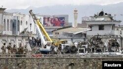 Petugas keamanan Afghanistan memeriksa lokasi ledakan bom di Kabul, Afghanistan (19/4).
