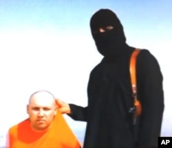 FILE - This image from an undated video released by Islamic State militants Aug. 19, 2014, purports to show journalist Steven Sotloff, who had been captured in Aleppo, being held by the militant group. He was later beheaded.