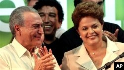 Brazil's President-elect Dilma Rousseff, right, smiles as Vice President-elect Michel Temer applauds upon her arrival to give her victory speech after winning the election runoff in Brasilia, Brazil, 31 Oct. 2010.
