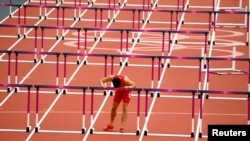 China's Liu Xiang leans against the last hurdle after crashing out of the heats in the 110 meter hurdles at the 2012 London Olympics. REUTERS/David Gray