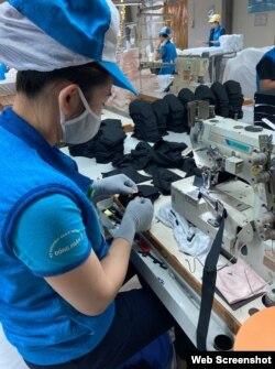 Một công nhân nhà máy dệt kim Đông Xuân đang may khẩu trang. Photo US Embassy Hanoi